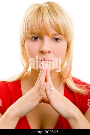 Junge Frau presst ihre Fingerspitzen aneinander - Stock Photo