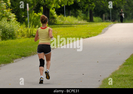 Female jogger with knee brace. - Stock Photo