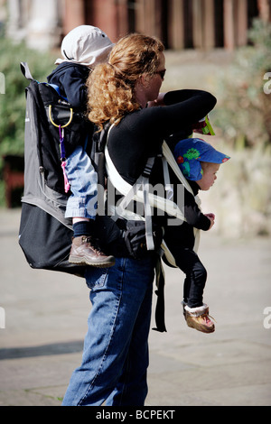A mother with two children strapped to her in Coventry, UK - Stock Photo