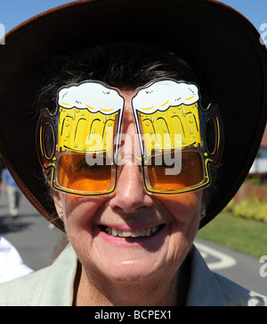 Woman wearing comic beer sunglasses at Ferring village community garden day in Sussex - Stock Photo