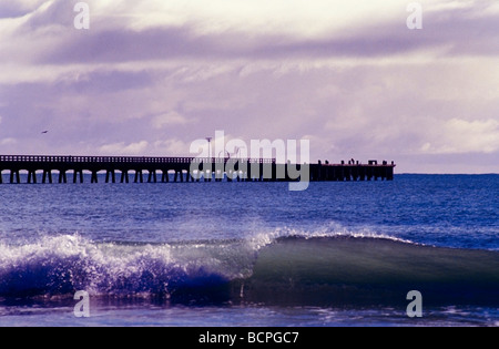 Tolaga Bay with wharf with small wave breaking on the beach in the foreground East Coast New Zealand - Stock Photo