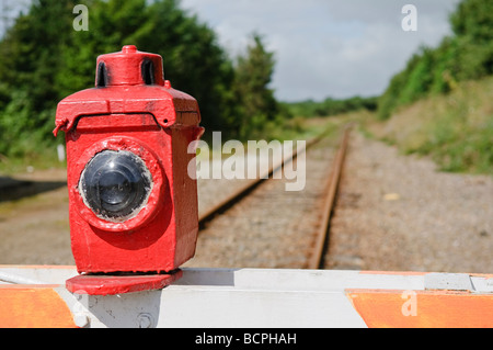 Manually operated level crossing barrier with paraffin warning lamp light across a train railway track - Stock Photo