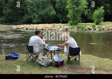 Older Couple Having A Picnic In Front Of Their Classic