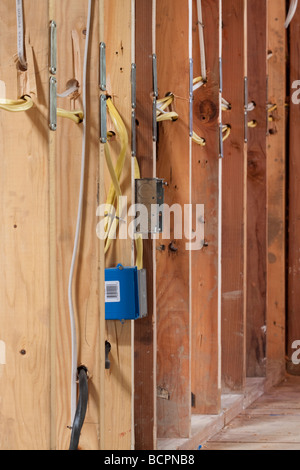 Many electrical wires running through wall studs and connecting to a metal outlet box at residential construction - Stock Photo