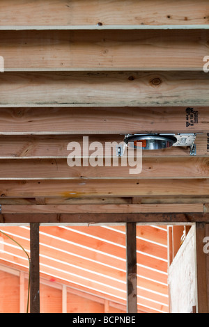 Electrical wires running through wall studs and connecting to outlet boxes at residential construction site - Stock Photo