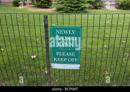 A sign on a railing reads Newly seeded lawn please keep off in Central Park in New York USA 31 May 2009 - Stock Photo