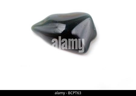 Cutout of a Bloodstone gemstone on white background - Stock Photo