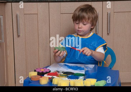 three year old boy at small table in kitchen playing with paint brushes and sponges, art and craft - Stock Photo