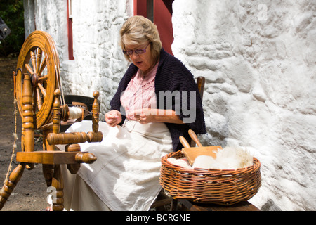 Woman using a spinning wheel, Ulster American Folk Park, Omagh, Northern Ireland - Stock Photo