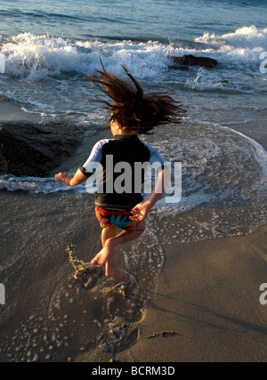 Young girl playing and jumping in the waves on the beach. Happy childhood memories of fun - Stock Photo