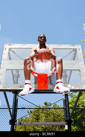Handsome sporty African American male basketball player dressed in white and holding his ball outdoor on a summer day