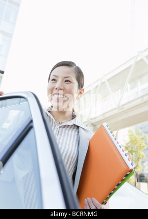 Businesswoman getting out of taxi - Stock Photo
