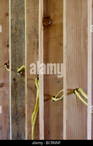 Electrical wires running through wood wall studs at residential construction site - Stock Photo
