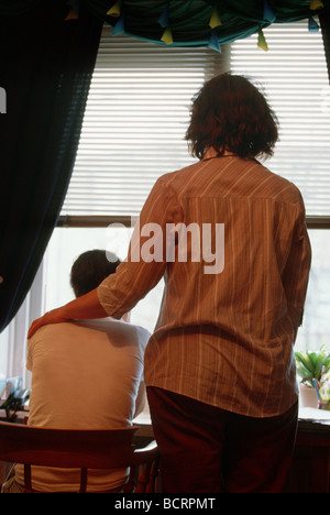 Back view from mid aged mother comforting young adult son at home. SerieCVS117004 - Stock Photo