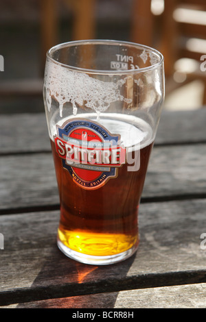 A half full pint of beer in summer sun - Stock Photo