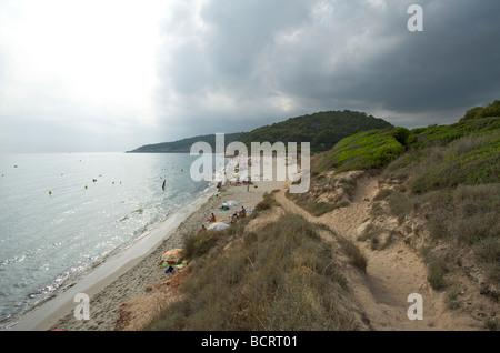 Storm clouds gather behind the beach of Binigaus Menorca - Stock Photo