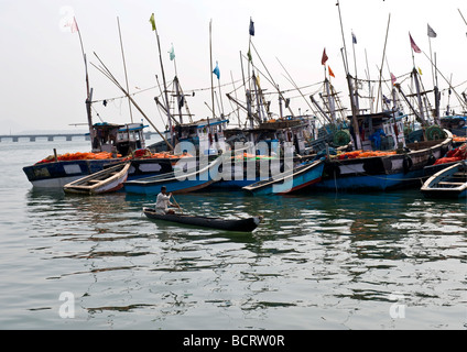 Man in a canoe patrolling serviced Indian fishing boats anchored and tied in line at quay prepared to sail for fishing - Stock Photo