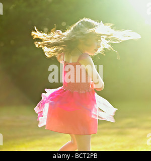 Young girl in a pink dress dancing in the garden summer sun. - Stock Photo