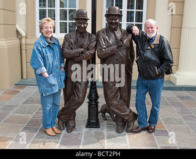 Tourists with memorial statue of Laurel and Hardy In Ulverston, Cumbria UK. - Stock Photo