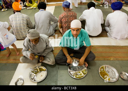 Sikh men eating a free meal served in the Community kitchen at the The Golden Temple (Sri Harmandir Sahib) Amritsar. - Stock Photo