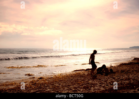 Warm Southern California summer afternoon, kids digging the sandy beach at San Clemente. - Stock Photo