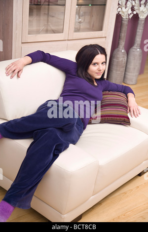 Girl lying on a cozy armchair - Stock Photo