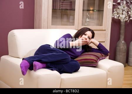 Girl lying on a cozy armchair, yawning - Stock Photo