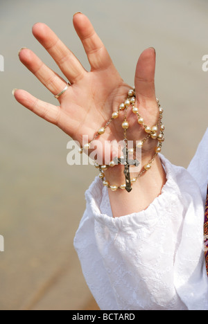 woman holding rosary by lake in her hand - Stock Photo