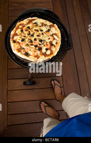 man cooking pizza on outdoor grill stock photo royalty free image 28862878 alamy. Black Bedroom Furniture Sets. Home Design Ideas
