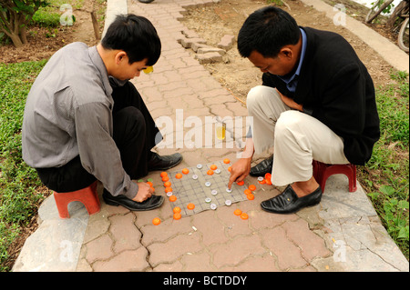 Two Vietnamese men playing chase and drinking tea in winter cold weather day, Hanoi, vietnam . - Stock Photo