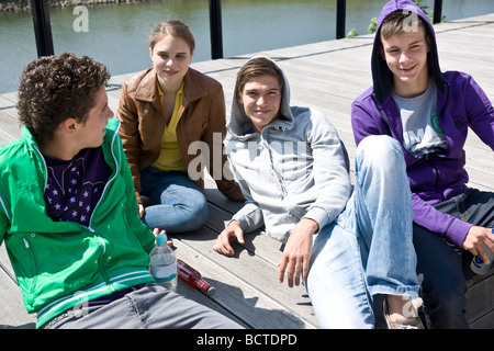 Three boys and a girl sitting on the floor, relaxing in the sun - Stock Photo