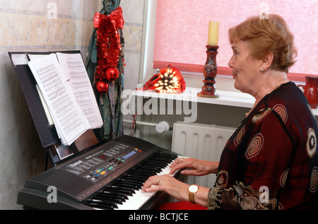 Christmas songs : Elderly lady play Christmas hymns on keyboard at home - Stock Photo