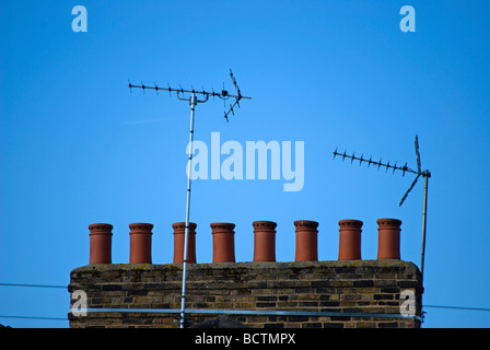 row of chimey pots and two tv aerials on a rooftop of victorian homes in barnes, southwest london, england - Stock Photo