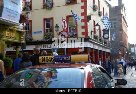 taxi with irish spelling tacsai on for hire board waiting for a fare outisde pubs in temple bar area in dublin city - Stock Photo