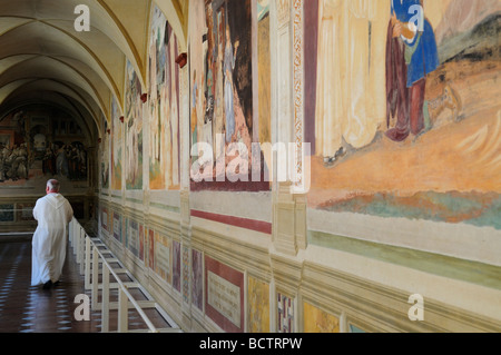 Olivetan monk walking past Renaissance frescos in Monte Oliveto Maggiore monastery, Tuscany Italy - Stock Photo