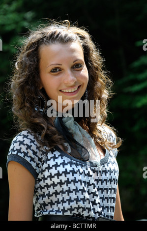 Portrait of a beautiful happy brunette teenage girl with curly hair - Stock Photo