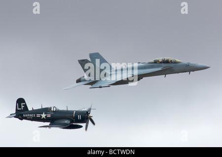 An FA 18 Hornet fighter jet flies alongside a world war II fighter during a heritage flight at the Miramar Airshow - Stock Photo