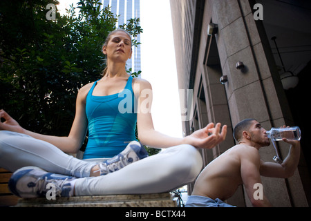 Low angle view of a young woman meditating with a young man drinking water behind her - Stock Photo