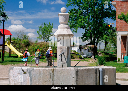 Spain, St. James Way: Pilgrims at the medieval fountain of Villambista - Stock Photo