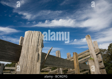 Old wooden stockyard fence with blue sky and clouds - Stock Photo