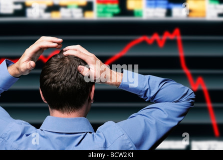 Stock Trader Clutching His Head in Front of a Screen Showing a Stock Market Crash - Stock Photo