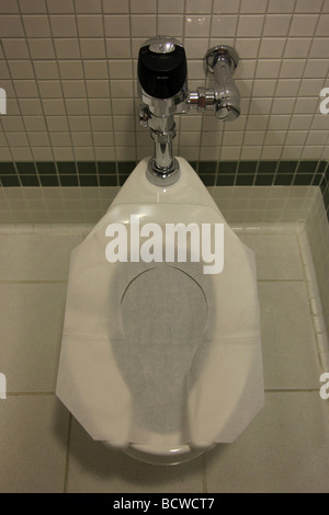 Health guard liner placed on a toilet seat in a public restroom - Stock Photo