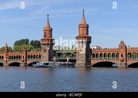Oberbaumbruecke bridge with passenger ships on the Spree river Berlin, Germany, Europe - Stock Photo