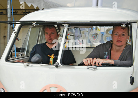 couple in Classic split screen VW bus with opening windscreen - Stock Photo