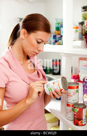 Woman looking at food label on back of tin - Stock Photo