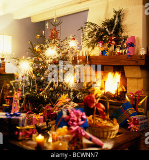 CHRISTMAS PRESENTS UNDER THE TREE WITH SPARKLERS AND FIREPLACE - Stock Photo