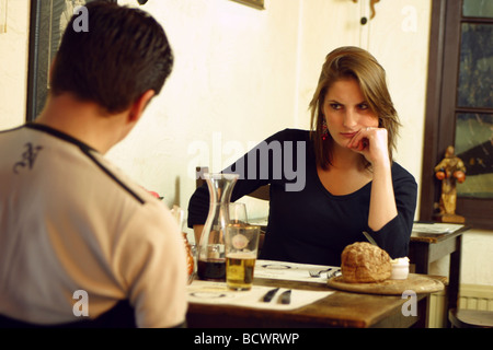 Young woman looking annoyed at boyfriend at table in restaurant. - Stock Photo