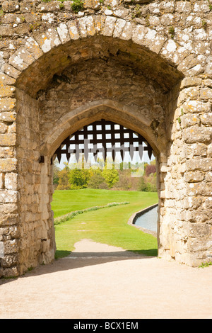Detail of medieval stone castle gate with grass and mote in the background - Stock Photo