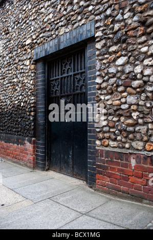 A black metal gate set into a stone wall. - Stock Photo