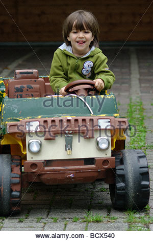 Little boy driving and playing with a toy electric car sit sitting green expensive toys plastic - Stock Photo